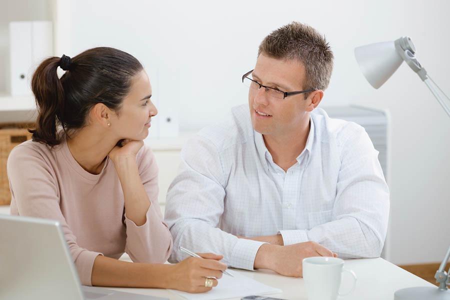 """Happy young casual couple sitting at desk working together at home office, smiling. Click here for more """"People at Home"""" images: [url=my_lightbox_contents.php?lightboxID=1507925][img]http://www.nitorphoto.com/istocklightbox/peopleathome.jpg[/img][/url]"""