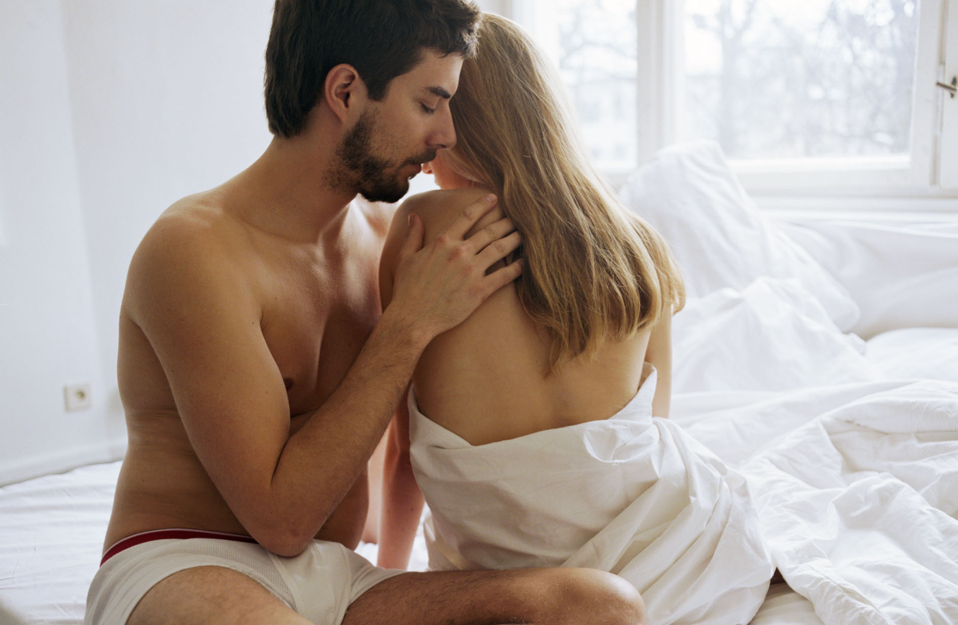 Young couple sitting on bed, man touching woman's shoulder