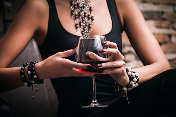 young elegant woman hold glass of red wine, indoor shot, selective focus